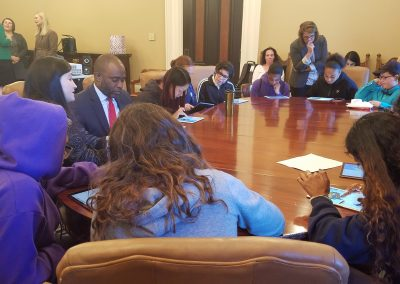 Students sitting with Tony Thurmond around a table for a coding demonstration