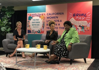 Photograph showing First Partner Jennifer Siebel Newsom, former Editor in Chief of Teen Vogue Elaine Welteroth and Assemblymember Shirley Webber seated in a semicircle in front of artwork and signs referencing Equal Pay California.